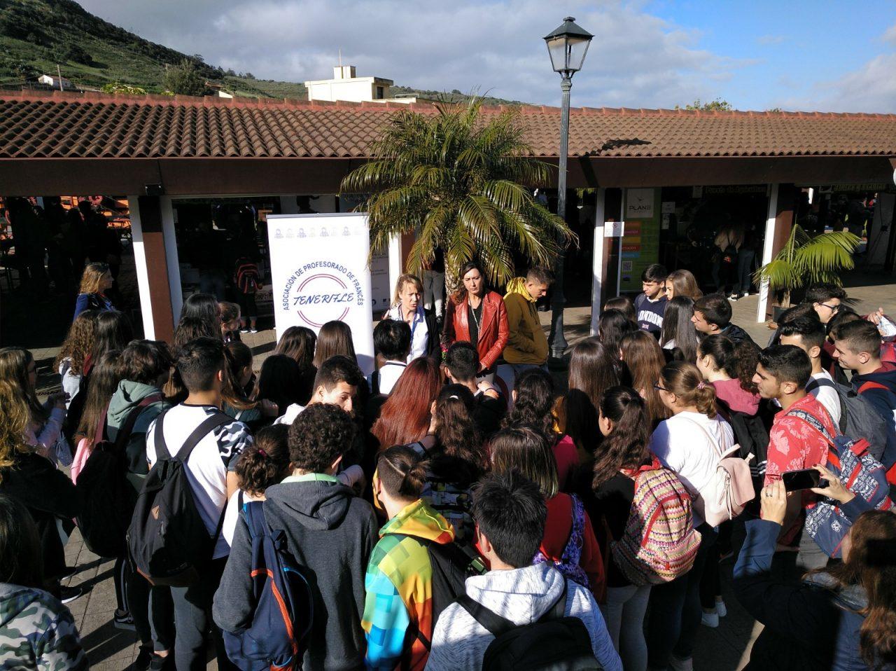 La 1ª Feria de las Profesiones Francófonas de Tenerife nos ha hecho disfrutar de un día diferente en el Mercado del Agricultor de Tegueste. La celebración, durante este mes de marzo de 2019 del Mes de la francofonía en Tenerife, ha supuesto que el mercadillo haya abierto sus instalaciones sin que tuviera lugar su actividad principal: la comercialización de productos locales. Un día diferente en el Mercado del Agricultor de Tegueste gracias al evento organizado por la Asociación de Profesores de Francés de Tenerife (TeneriFLE). Esta 1ª Feria de las Profesiones Francófonas de Tenerife ha conseguido traer a Tegueste a más de 360 alumnos de centros educativos de la isla de Tenerife, que cursan estudios de francés. Un día diferente en el Mercado del Agricultor de Tegueste que ha servido para promover el aprendizaje de la lengua francesa como punto de mejora de la empleabilidad. Pero también para que las empresas Canarias, que desarrollan proyectos y/o mantienen relaciones comerciales con países francófonos pudieran comunicar sus necesidades a los estudiantes. Nueve empresas, instituciones y ONG´s han dispuesto de un stand informativo en la nave central del Mercadillo de Tegueste en esta 1ª Feria de las Profesiones Francófonas de Tenerife englobada dentro de los actos del Mes de la francofonía. Participaron el Consulado General de Francia en España, Alianza Francesa de Santa Cruz de Tenerife, Ayuntamiento de Tegueste, Klingele Embalajes, ICEX España, Plan B Group, Departamento de Filología Clásica, Francesa, Árabe y Románica de la Universidad de La Laguna, Escuela Oficial de Idiomas de La Laguna, PROEXCA del Gobierno de Canarias, Fundación General de la Universidad de La Laguna y la ONG Asociación Humanitaria Maman África. Un día diferente en el Mercado del Agricultor de Tegueste marcado por la presencia de numerosa juventud, que inundó todo el recinto, y que mostró un gran interés por las propuestas planteadas.
